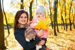 Femme avec la fille d'enfant en parc de ville d'autumun, famille heureuse Photographie stock