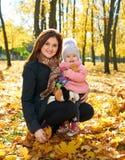 Femme avec la fille d'enfant en parc de ville d'autumun, famille heureuse Photographie stock libre de droits