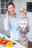 Femme avec la fille de transport de téléphone portable par le comptoir de cuisine Photos stock