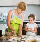 Femme avec la fille faisant cuire des boulettes de viande Images stock