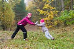 Femme avec la fille faisant l'aérobic en parc Photos libres de droits