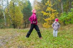 Femme avec la fille faisant l'aérobic en parc Photo stock