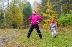 Femme avec la fille faisant l'aérobic en parc Photographie stock libre de droits