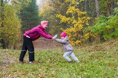 Femme avec la fille faisant l'aérobic en parc Photographie stock
