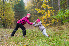 Femme avec la fille faisant l'aérobic en parc d'automne Image stock