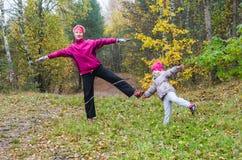 Femme avec la fille faisant l'aérobic en parc d'automne Image libre de droits
