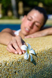 Femme avec la fleur détendant dans la piscine de jacuzzi de station thermale Image libre de droits