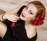 Femme avec la fleur rouge en portrait noir de robe Photo stock