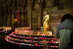Femme avec la foi de souvenirs de bougies dans le cathe de Strasbourg Notre-Dame photographie stock libre de droits