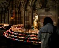 Femme avec la foi de souvenirs de bougies dans le cathe de Strasbourg Notre-Dame images libres de droits