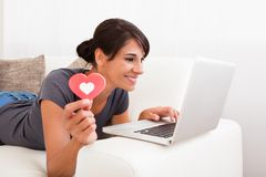 Femme avec la forme et l'ordinateur portable de coeur Image libre de droits