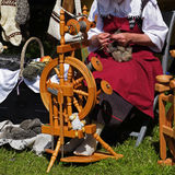 Femme avec la laine à la roue de rotation traditionnelle sur un médiéval Images stock
