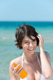 Femme avec la lotion de bronzage à la mer Images stock