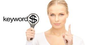 Femme avec la loupe et le mot de mots-clés Photo stock