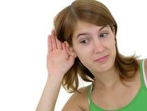 Femme avec la main à l'écoute d'oreille Photos stock