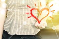 Femme avec la main ouverte tenant une icône de forme de coeur dans un jour ensoleillé Image libre de droits