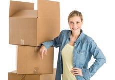 Femme avec la main sur la hanche se penchant sur les boîtes en carton empilées Images libres de droits