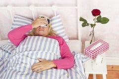 Femme avec la migraine se situant dans le lit Photographie stock libre de droits