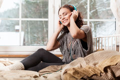 Femme avec la musique de écoute d'écouteurs photographie stock libre de droits