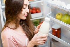 Femme avec la nourriture près du réfrigérateur Images libres de droits