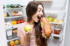 Femme avec la nourriture près du réfrigérateur Photographie stock libre de droits
