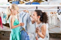 Femme avec la petite fille choisissant les vêtements bleus Image stock