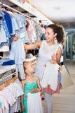 Femme avec la petite fille choisissant les vêtements bleus Photo stock