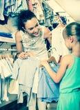 Femme avec la petite fille choisissant les vêtements bleus Photo libre de droits