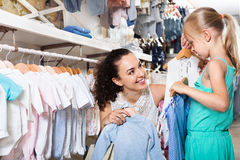 Femme avec la petite fille choisissant les vêtements bleus Images stock