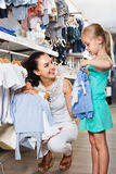 Femme avec la petite fille choisissant les vêtements bleus Photos stock