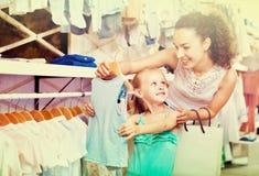 Femme avec la petite fille choisissant les vêtements bleus Images libres de droits