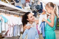 Femme avec la petite fille choisissant les vêtements bleus Photos libres de droits