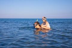Femme avec la petite fille ferroutant avec les verres de plongée dans l'eau d'une plage en Andalousie image stock