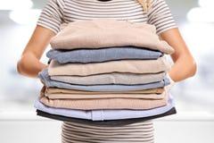 Femme avec la pile des vêtements repassés et emballés Photos libres de droits