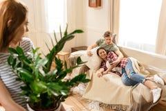 Femme avec la plante verte dans le pot regardant des couples utilisant le smartphone sur le sofa Image libre de droits