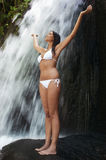 Femme avec la position augmentée par bras sur la roche par la cascade Photo stock