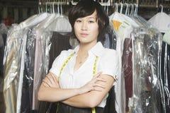 Femme avec la position croisée par bras contre le rail de vêtements dans la blanchisserie photos libres de droits