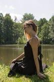 Femme avec la robe noire sur le lac Images stock