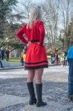 Femme avec la robe rouge observant le carnaval avec des confettis Photo stock