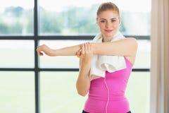 Femme avec la serviette autour du cou étirant la main dans le studio de forme physique Photos libres de droits
