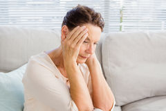 Femme avec la tête dans des mains tout en se reposant sur le sofa Photos stock