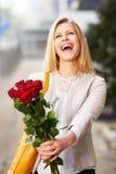 Femme avec la tête inclinée tenant des roses photographie stock libre de droits