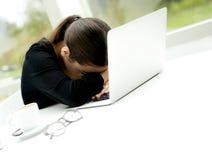 Femme avec la tête sur l'ordinateur portable Image libre de droits