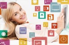 Femme avec la tablette et les icônes à la maison futées image libre de droits