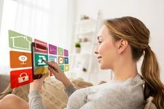 Femme avec la tablette et les icônes à la maison futées images stock