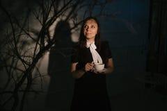 Femme avec la tasse de café dans l'endroit foncé image stock