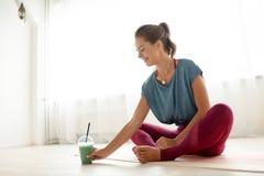 Femme avec la tasse du smoothie au studio de yoga image stock