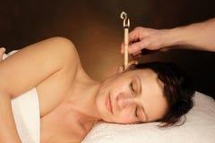 Femme avec la thérapie de bougie d'oreille Photographie stock libre de droits