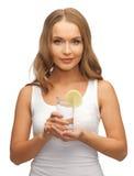 Femme avec la tranche de citron sur le verre de l'eau Photos libres de droits