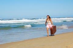 Femme avec la valise sur la plage Images stock